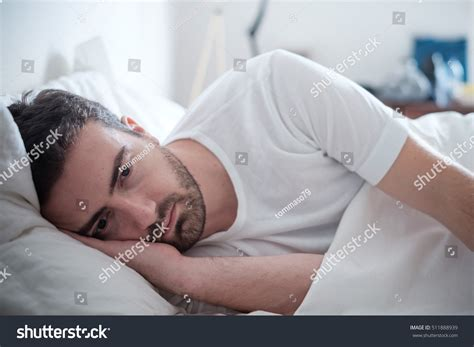 lying in my bed depressed man lying his bed feeling stock photo 511888939
