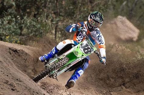 motocross gear combos rider hits banked corner on kawasaki kx250f wearing answer