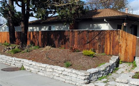 we repurposed concrete rip rap and created a retaining wall we also reused redwood fence boards