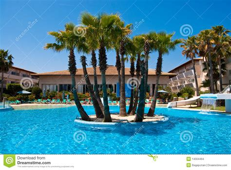 Mediterranean Home Plans hotel swimming pool with the palm island stock photo