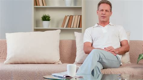a man and a couch nice man sitting on the couch stock footage video 15902521