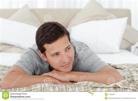 lying on the bed happy man lying on the edge of his bed stock image image