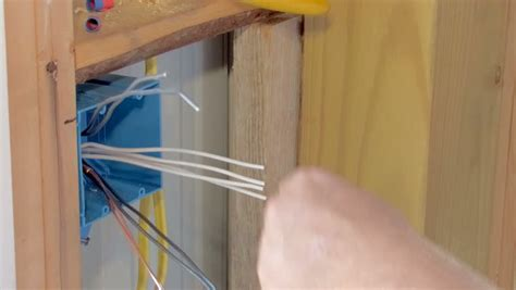 electrician wiring wall outlet box in new construction