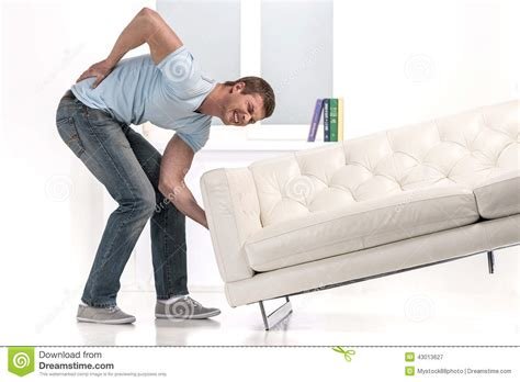 lift couch handsome man lifting sofa and feeling pain stock image