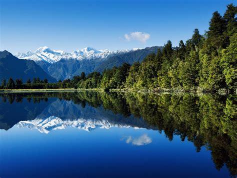 summer landscape green mountain pine forest  snow blue sky reflected  lake  zealand hd