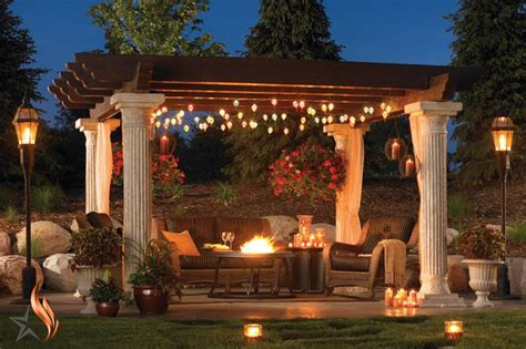 Pergola Over An Outdoor Gas Fire Glass Pit With Hanging Lights On Pergola