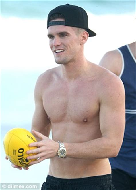 Shirtless Gary Beadle frolics on the beach with DJ