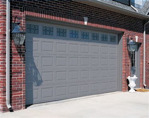 brick house with a garage door and front door color gray and front door