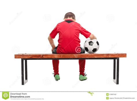 seated bench rear view of a sad little boy in soccer jersey stock photo