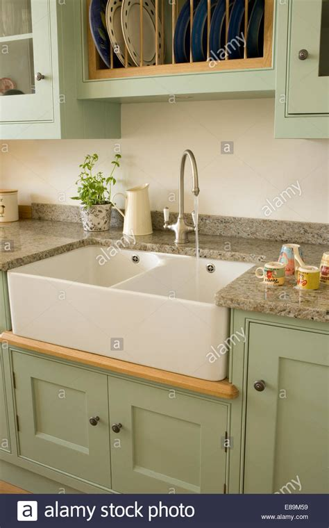 kitchens with belfast sinks chrome tap above double belfast sink in pale green units
