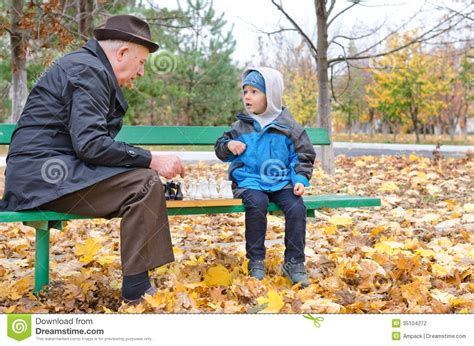 back bench boys grandfather playing chess with his little boy stock photo