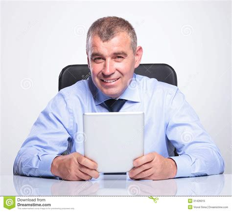 Man Sitting At A Desk Old Business Man At Desk Holds His Tablet Royalty Free