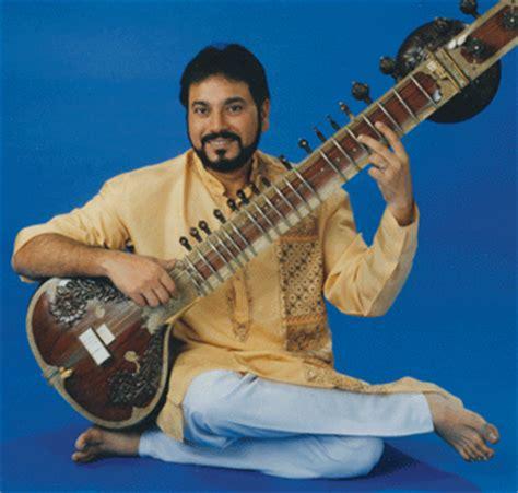 indian man kushal das playing a sitar.