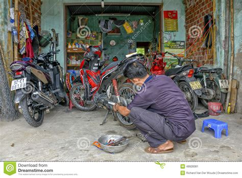 motor scooter repair motorcycle mechanic repairing flat tire scooter editorial