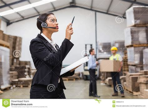 warehouse manager wearing headset checking inventory stock photo image 49902414