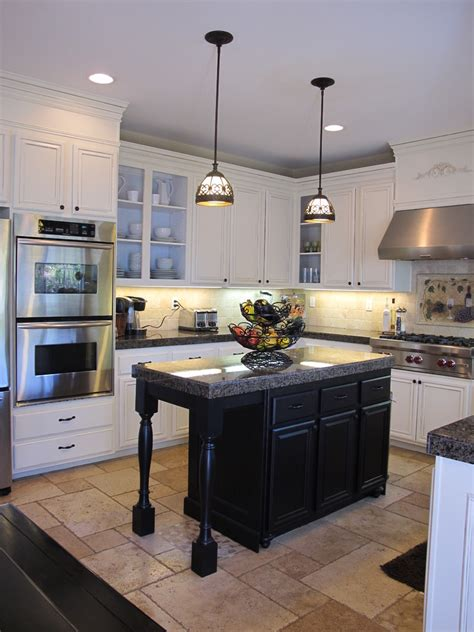 white kitchen cabinets with black island hanging lights over island in kitchen