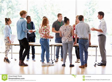 students in desks with college students standing by desks in classroom stock photo image 47103529