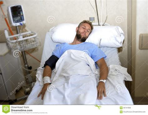guy in hospital bed injured man lying in bed hospital room resting from pain