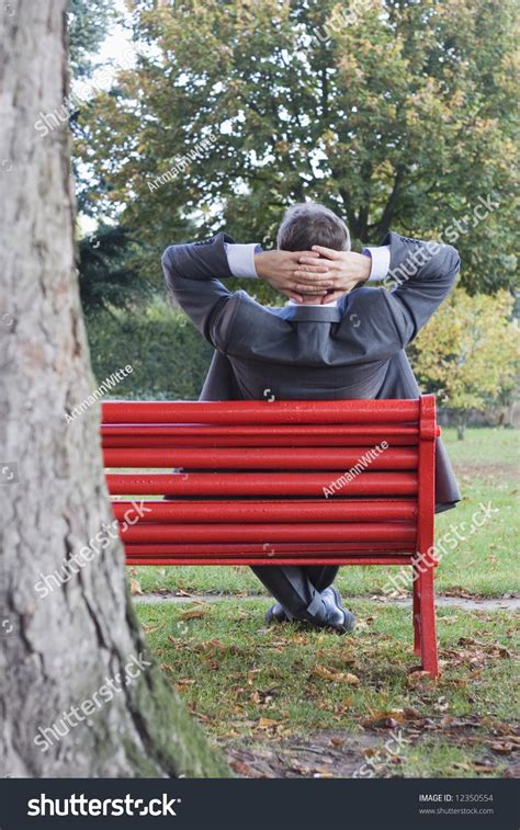 red park bench businessman relaxing on a red park bench stock photo