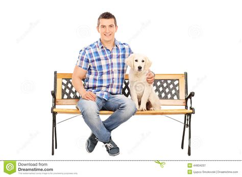 guy sitting on bench casual man sitting on a bench with a puppy stock image