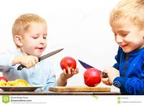 little boys cutting apple with a kitchen knife stock photo