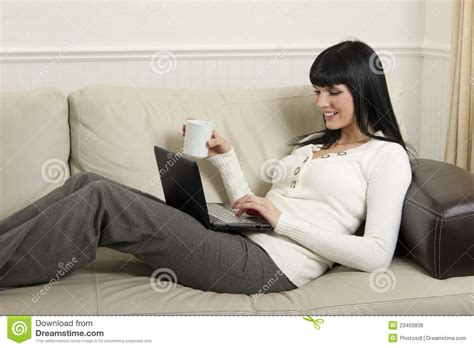 in the comfort of my home woman relaxing at home with her computer stock photo