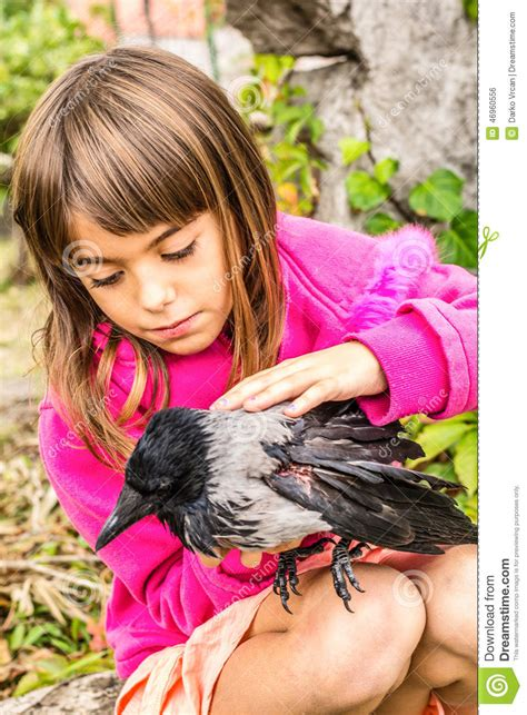 tiny petite crow and a little girl stock photo image 46960556