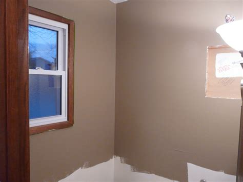 calm room design idea with earth tone wall paint color and single hung window white trim