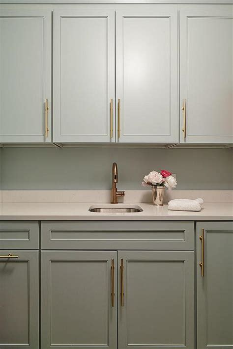 gray laundry room cabinets with brass pulls