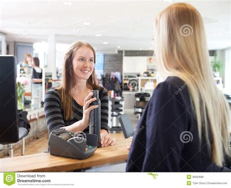 receptionist and client in beauty salon stock photo