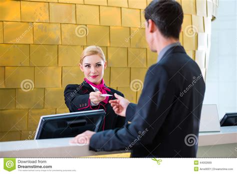 hotel receptionist check in giving key card stock