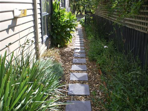 side of the house the path to the side of the house after laying pavers and pebbles looking from the