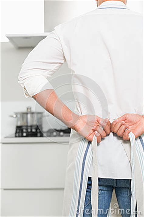 c section apron mid section of a man wearing apron in kitchen royalty free
