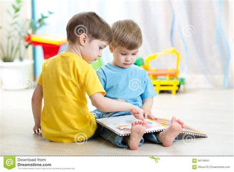 Daycare Floor Plans children read a book sitting on floor at home stock photo