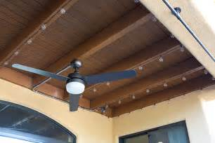 String lights and outdoor ceiling fan on a covered patio