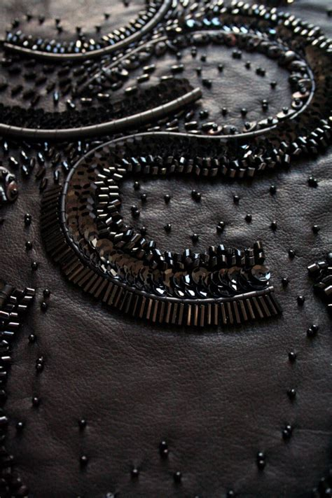 beaded embellishment on black leather with curved patterns