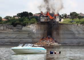 The water by their boat as they watch the house burn on the cliff edge