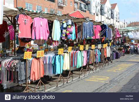 In The Fashion Marketplace by Romford Market Stall With Bargain Clothing On Hanging