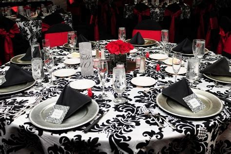 Wedding reception decor. Damask tablecloths, small red