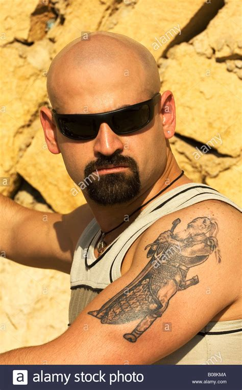 tattoo photo stock portrait of a skinhead man with goatee and arm tattoo