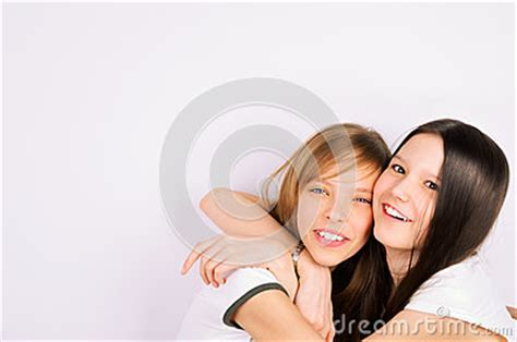 blonde and brunette teen girls cuddling and laughi stock