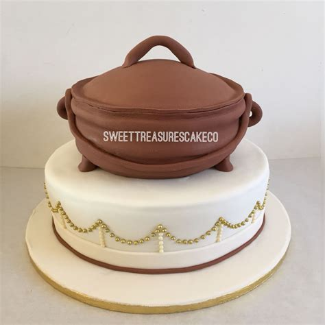 Traditional wedding cake. African cooking pot on gold