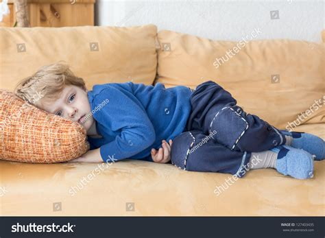 laying on the couch tired toddler boy laying on couch stock photo 127403435