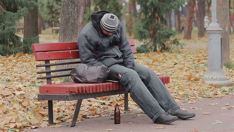 bench drinking homeless alcoholic woman drinking wine and coughing on a