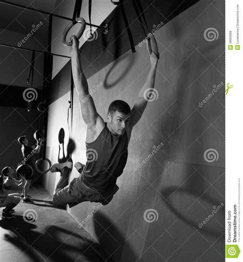 swinging gym muscle ups rings man swinging workout at gym stock photo