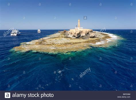 small boat big ocean small island and reef in ocean lighthouse and dive boats