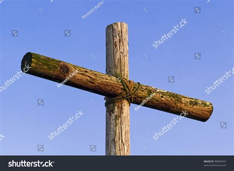 rugged cross in an rugged wooden cross stands against a blue sky stock photo 98699324