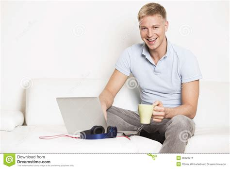 Room Online Free joyous man sitting on couch with laptop and drinking