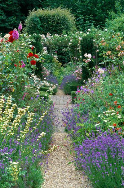 country cottage garden in summer gravel path with mixed