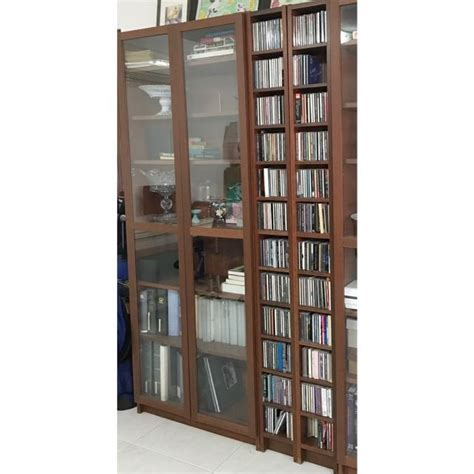 ikea billy bookcase with glass doors and two cd towers in